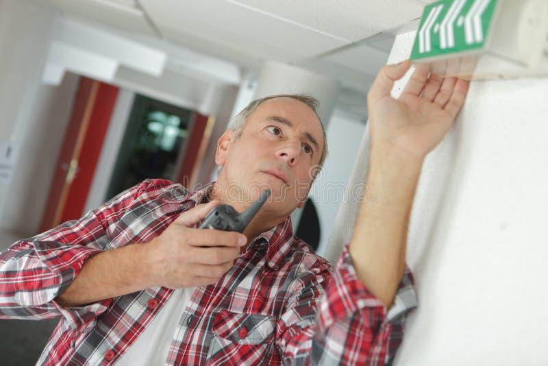 Uomo con il walkie-talkie che controlla il sistema di emergenza al sito immagine stock libera da diritti