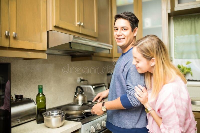 Uomo con l'amica che cucina in una cucina fotografie stock libere da diritti
