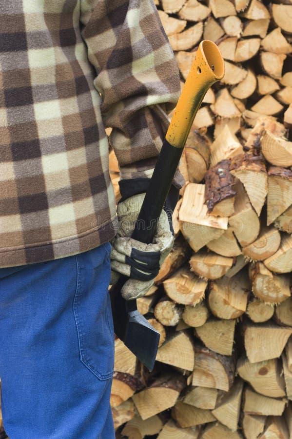Uomo con l'ascia e la legna da ardere tagliata immagine stock libera da diritti