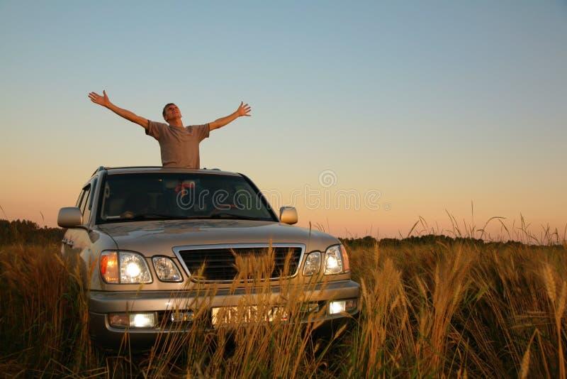 Uomo con l'automobile fuori strada nel campo fotografia stock libera da diritti