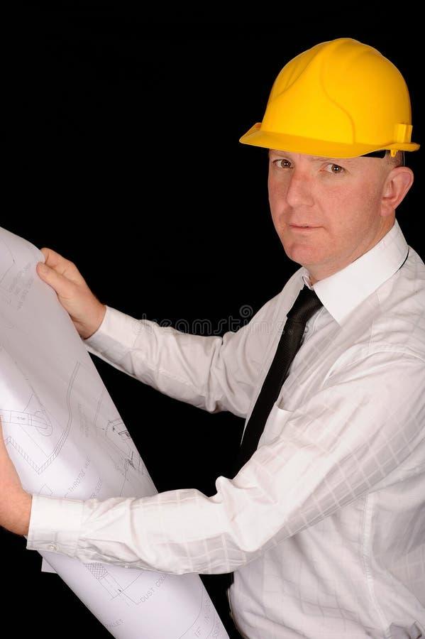 Uomo con l'elmetto protettivo e la cianografia immagini stock libere da diritti
