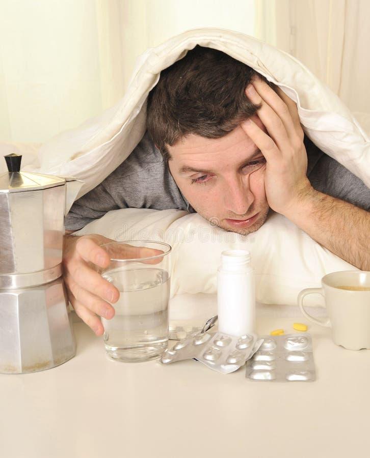 Uomo con l'emicrania ed i postumi di una sbornia a letto con le compresse fotografie stock