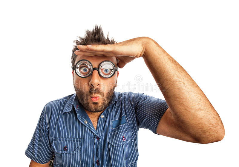 Uomo con l'espressione divertente ed i vetri spessi che guardano lontano immagini stock