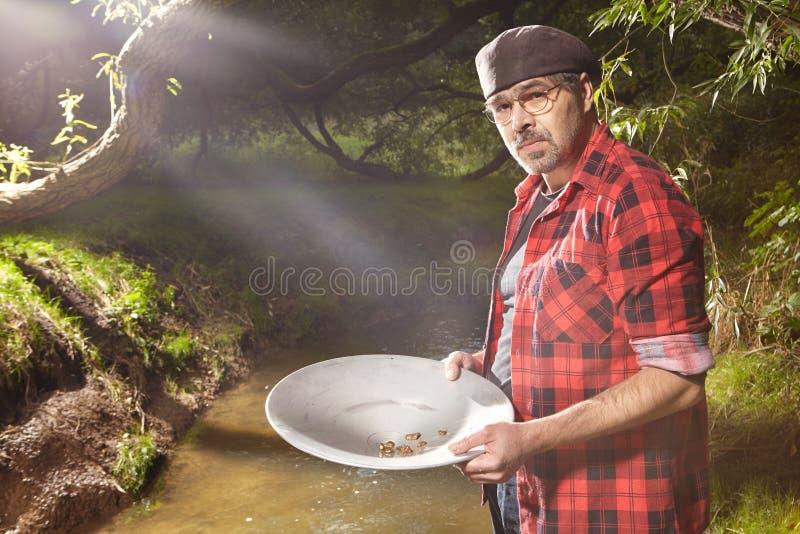 Uomo con l'insenatura di alluminio di cottura della pentola per oro immagini stock