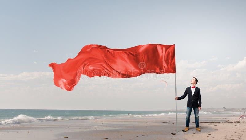 Uomo con la bandiera d'ondeggiamento rossa fotografia stock libera da diritti