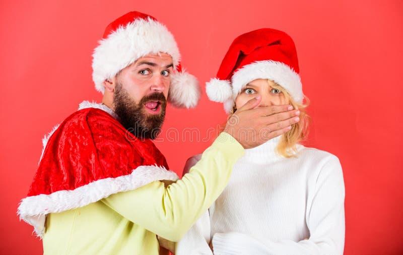 Uomo con la barba e donna in cappello di Santa su fondo rosso L'uomo copre la bocca della ragazza per tenere segreto Le coppie ce fotografia stock libera da diritti
