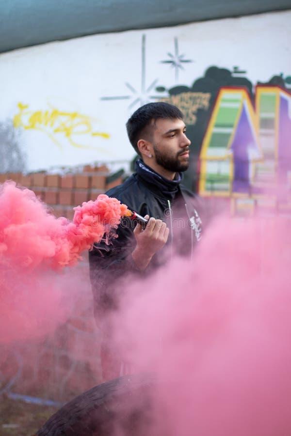 Uomo con la barba e l'attrezzatura urbana che tengono un chiarore rosso del fumo fotografie stock