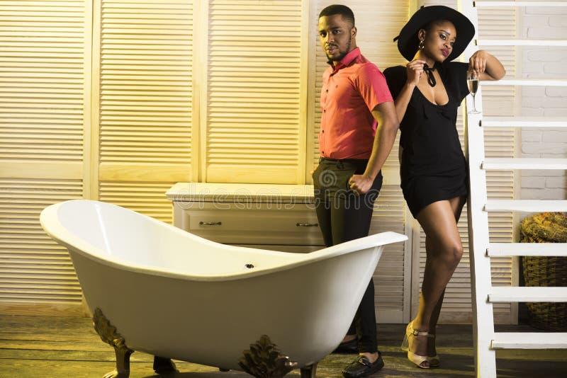 Uomo con la barba e signora in cappello con vetro di champagne in bagno Coppie sui fronti calmi che si rilassano nel bagno lusso immagini stock libere da diritti