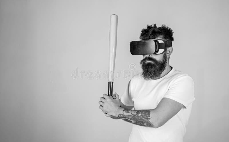 Uomo con la barba lunga concentrata sul gioco di realtà virtuale Uomo barbuto negli occhiali di protezione di VR che impara baseb fotografia stock libera da diritti