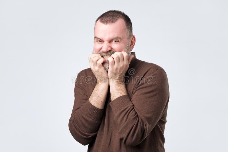 Uomo con la barba nelle unghie mordenti della camicia marrone nel timore fotografia stock