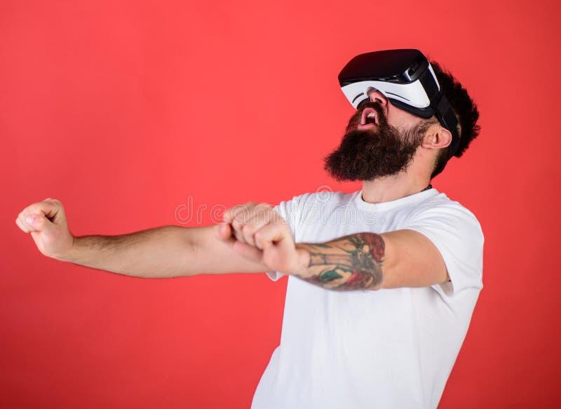 Uomo con la barba in vetri di VR che conducono motocicletta, fondo rosso Pantaloni a vita bassa sul fronte emozionante che conduc fotografia stock libera da diritti
