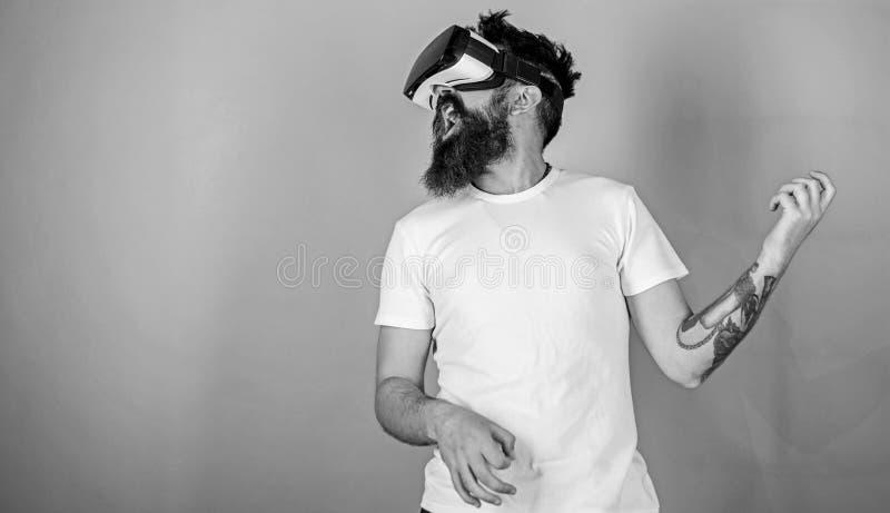 Uomo con la barba in vetri di VR, fondo verde Chitarrista dei pantaloni a vita bassa su tecnologia moderna di uso entusiasta del  immagine stock