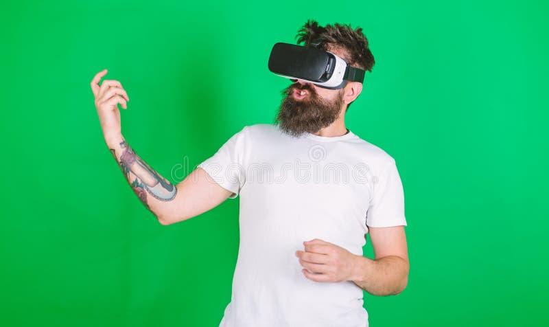 Uomo con la barba in vetri di VR, fondo verde Chitarrista dei pantaloni a vita bassa su tecnologia moderna di uso entusiasta del  immagini stock