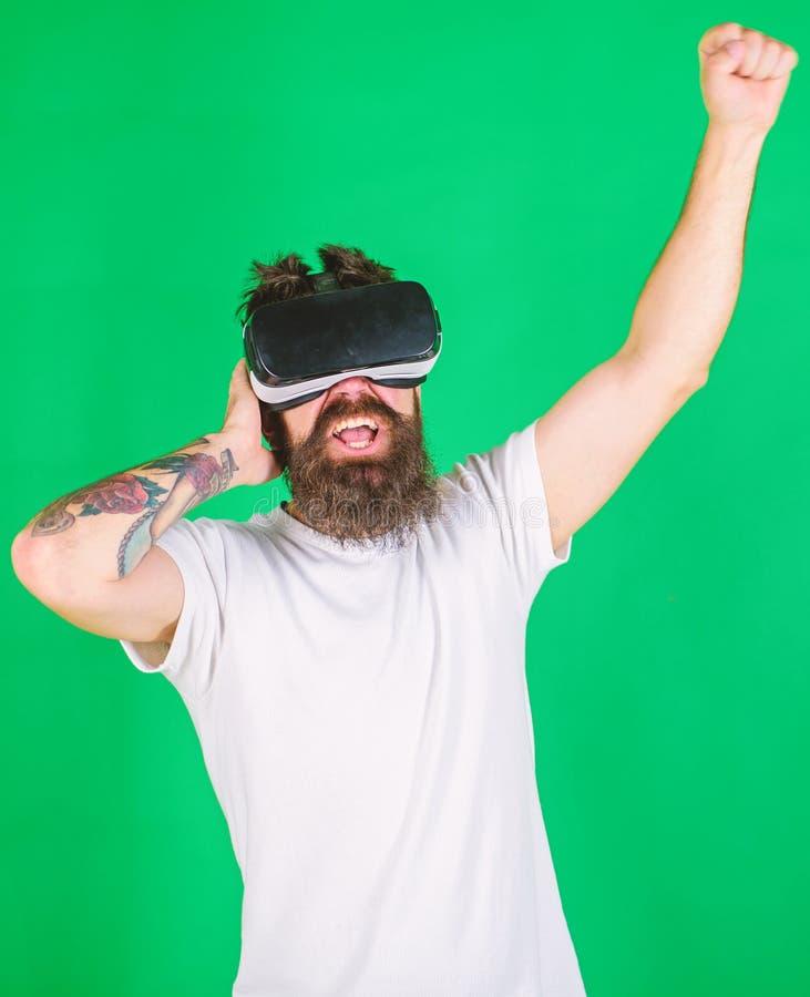 Uomo con la barba in vetri di VR, fondo verde Pantaloni a vita bassa sulle tecnologie moderne di uso entusiasta del fronte per sp fotografie stock