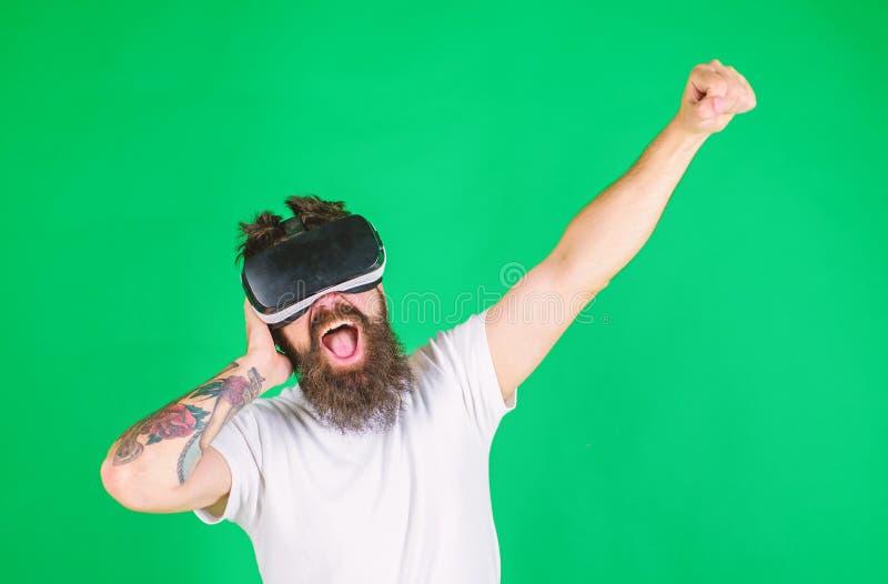 Uomo con la barba in vetri di VR, fondo verde Pantaloni a vita bassa sulle tecnologie moderne di uso entusiasta del fronte per sp fotografia stock libera da diritti