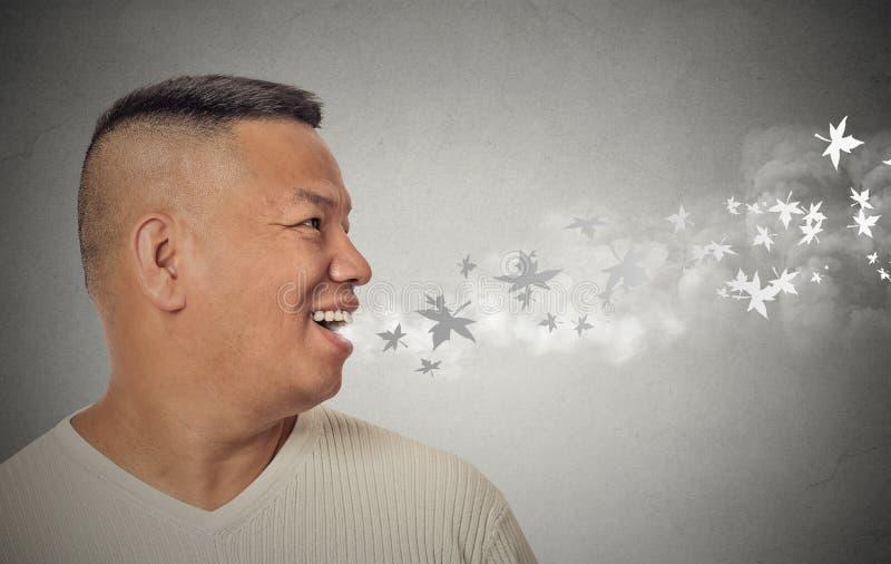 Uomo con la bocca aperta che soffia i fiocchi di neve freddi della brezza che volano via fotografia stock