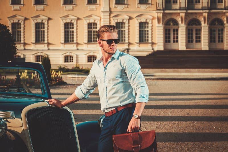 Uomo con la cartella vicino al convertibile classico fotografia stock