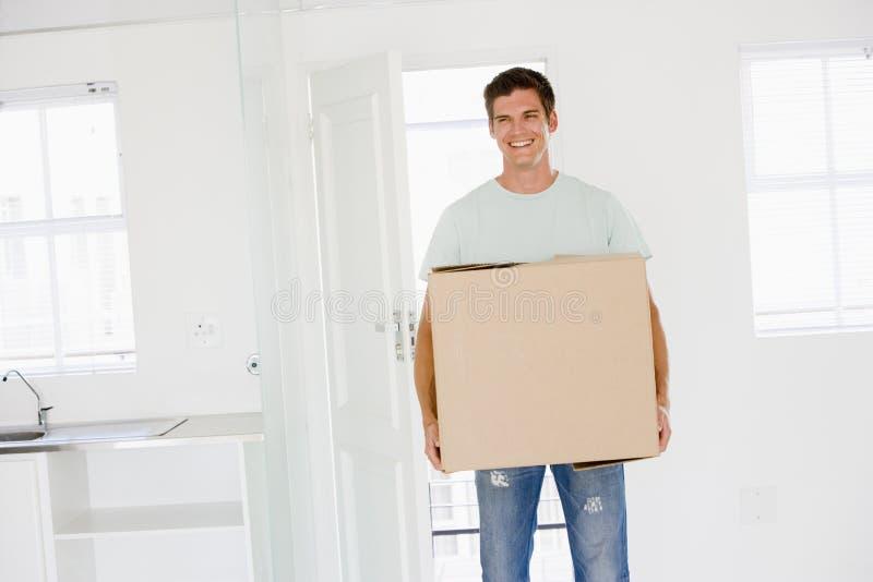 Uomo con la casella che entra nel nuovo sorridere domestico fotografie stock libere da diritti