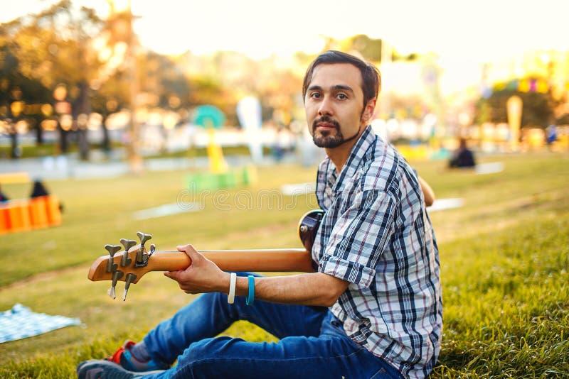 Uomo con la chitarra sull'erba fotografia stock libera da diritti