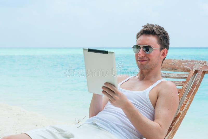 Uomo con la compressa sulla spiaggia, vista del mare fotografia stock libera da diritti