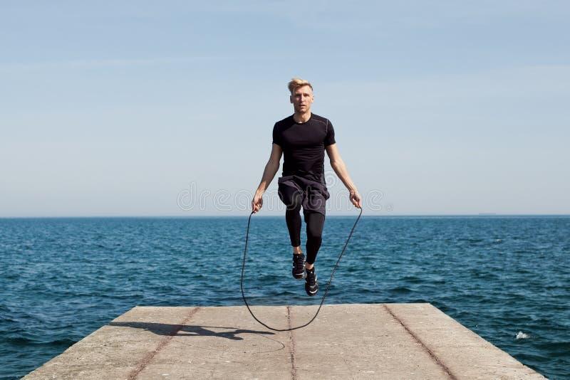 Uomo con la corda di salto sul pilastro immagine stock