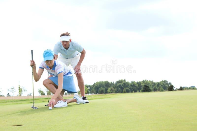 Uomo con la donna che tende palla sul campo da golf contro il cielo fotografia stock libera da diritti