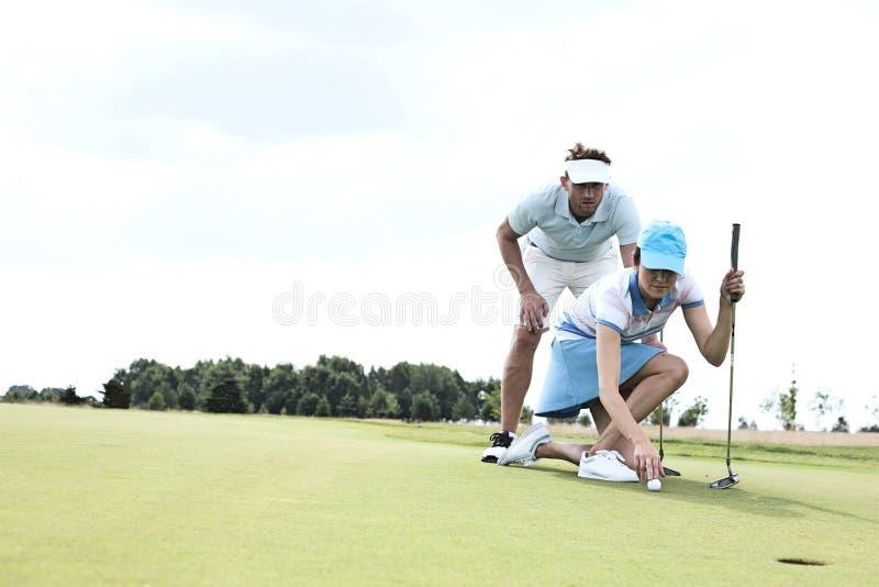 Uomo con la donna che tende palla sul campo da golf contro il cielo fotografia stock