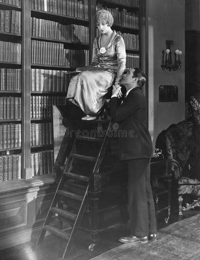 Uomo con la donna sulla scala in biblioteca (tutte le persone rappresentate non sono vivente più lungo e nessuna proprietà esiste immagine stock libera da diritti