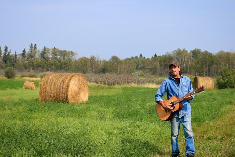 Uomo con la a e chitarra acustica nel campo immagine stock libera da diritti