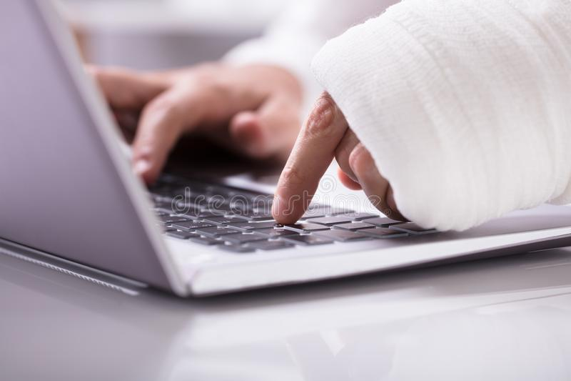 Uomo con la fasciatura avvolta sulla sua mano facendo uso del computer portatile immagine stock libera da diritti