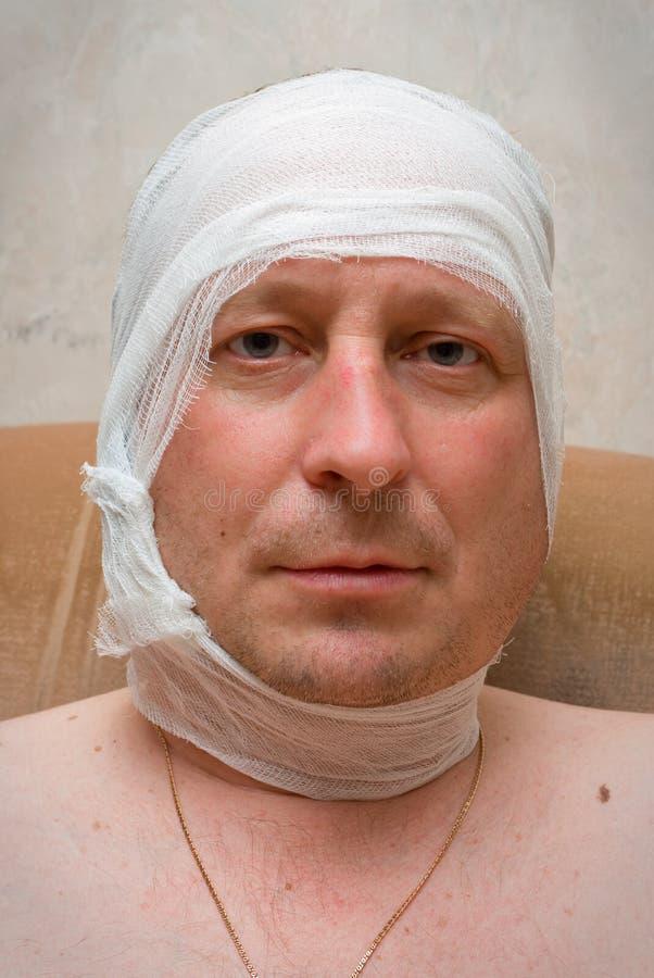 Uomo con la fasciatura sulla testa. fotografia stock libera da diritti