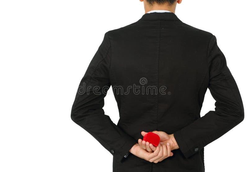 Uomo con la fede nuziale ed il contenitore di regalo rosso immagini stock