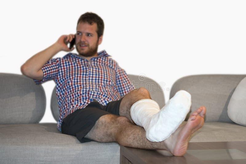 Uomo con la gamba fratturata che si siede su Sofa Talking On Cellphone fotografie stock