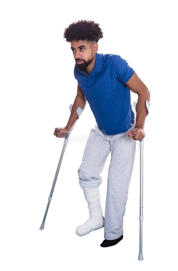 Uomo con la gamba rotta facendo uso delle grucce fotografia stock