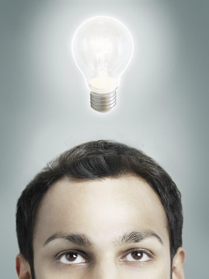 Uomo con la lampadina di Lit sopra la sua testa immagini stock libere da diritti