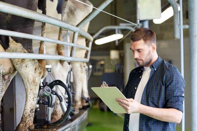 Uomo con la lavagna per appunti e le mucche di mungitura sull'azienda lattiera fotografie stock