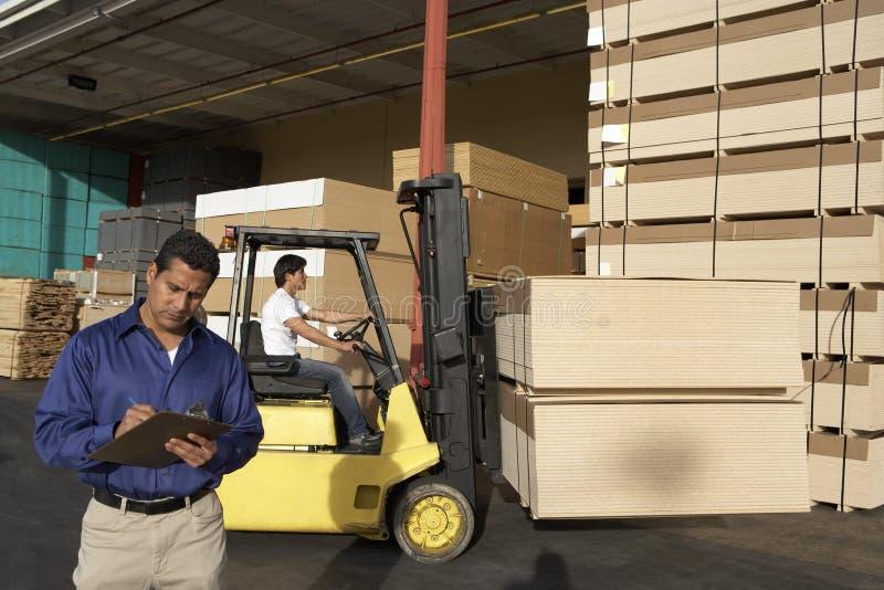 Uomo con la lavagna per appunti in Front Of Forklift Stacking Boxes immagine stock libera da diritti