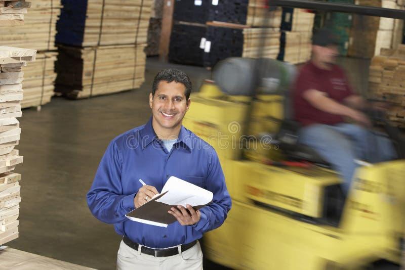 Uomo con la lavagna per appunti in Front Of Forklift In Warehouse fotografie stock libere da diritti