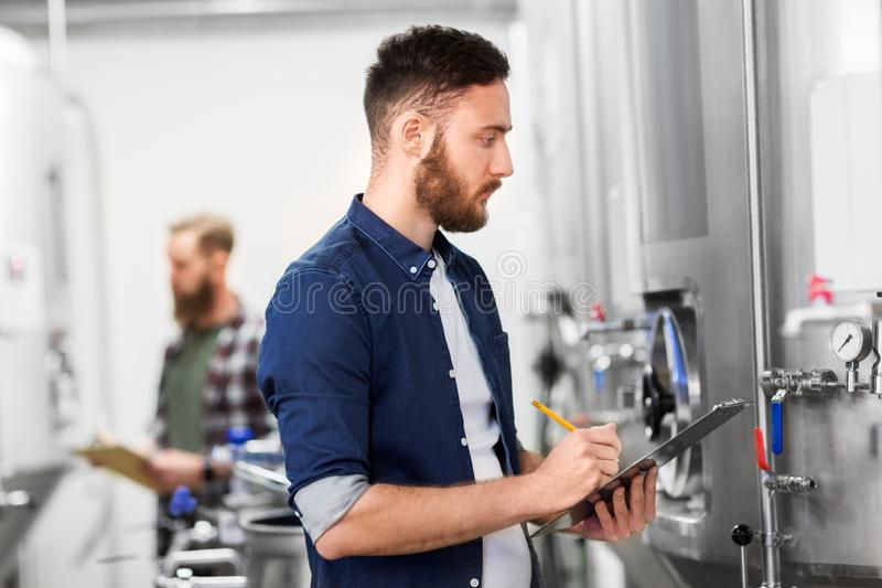 Uomo con la lavagna per appunti nella fabbrica di birra del mestiere o nella pianta della birra fotografie stock
