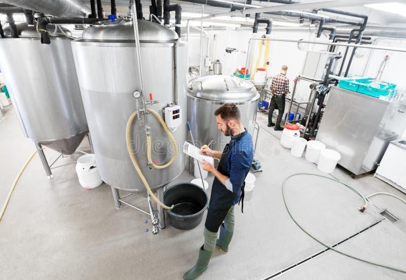 Uomo con la lavagna per appunti nella fabbrica di birra del mestiere o nella pianta della birra fotografia stock