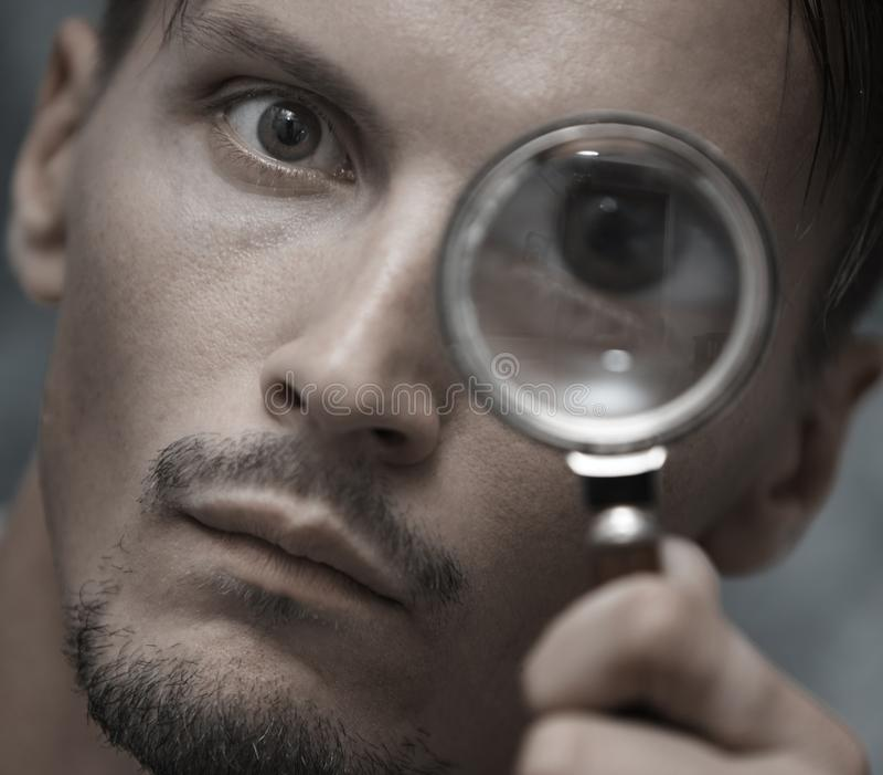 Uomo con la lente d'ingrandimento fotografie stock