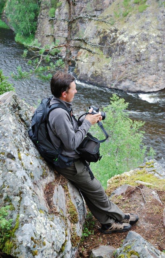 Uomo con la macchina fotografica sulla roccia sopra il fiume della montagna. immagine stock