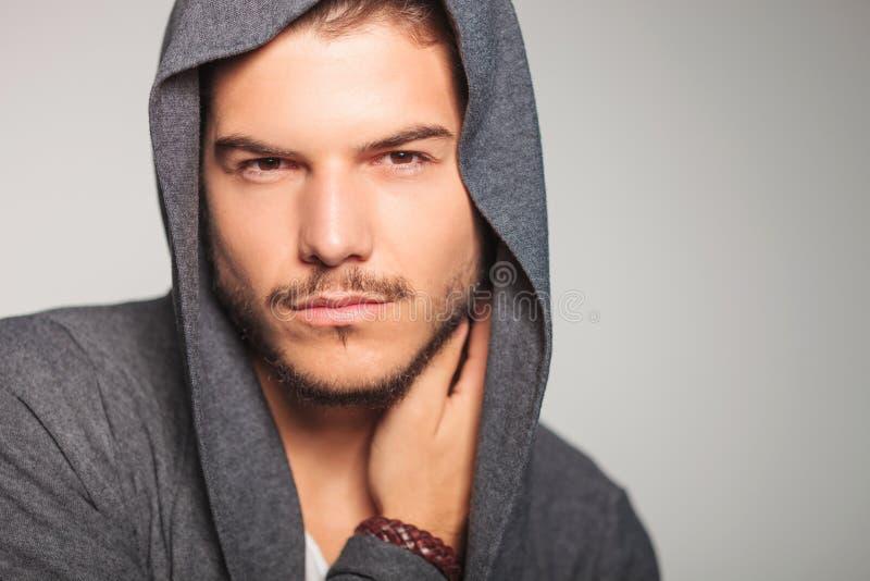 Uomo con la maglia con cappuccio sulla mano della tenuta sul collo fotografie stock libere da diritti
