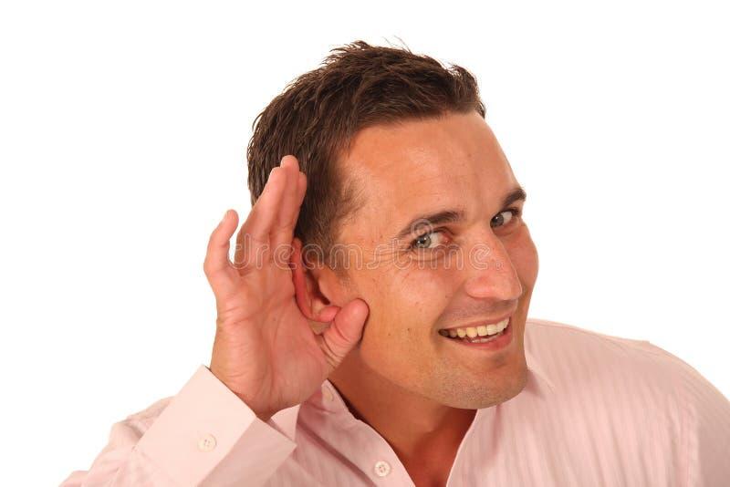 Uomo con la mano all'orecchio fotografia stock libera da diritti