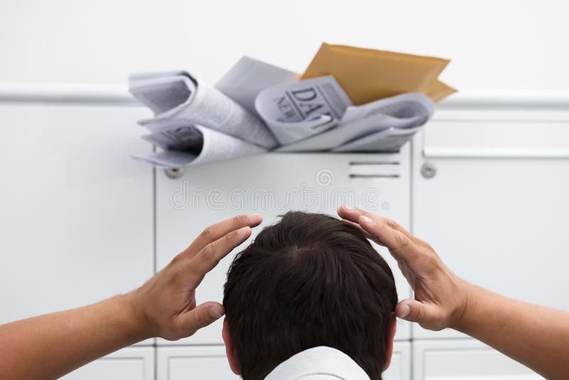 Uomo con la mano sulla testa davanti alla cassetta delle lettere sovraccaricata fotografia stock
