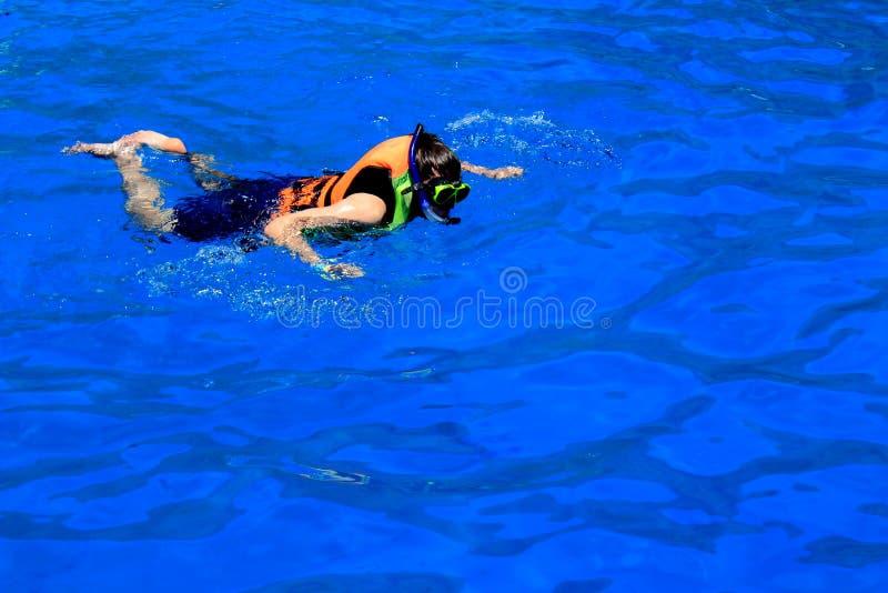 Uomo con la maschera che si immerge ed in acqua blu immagine stock