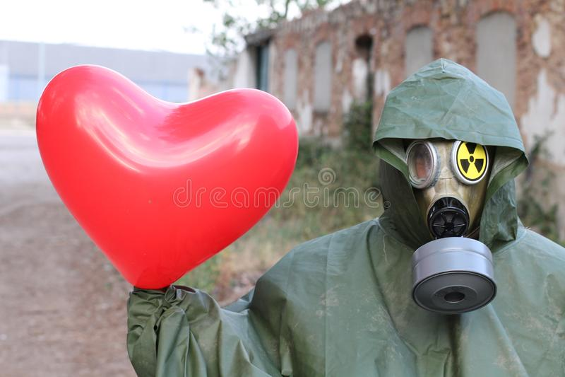 Uomo con la maschera di inquinamento che tiene un cuore fotografia stock libera da diritti