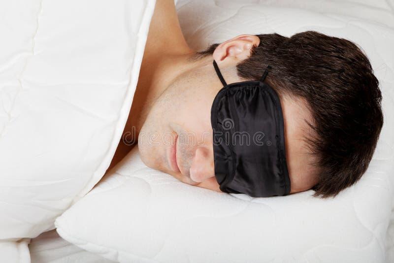 Uomo con la maschera di sonno che si trova a letto fotografia stock libera da diritti