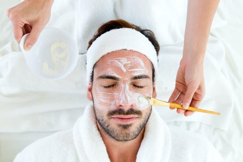 Uomo con la mascherina facciale dell'argilla nella stazione termale di bellezza immagini stock libere da diritti