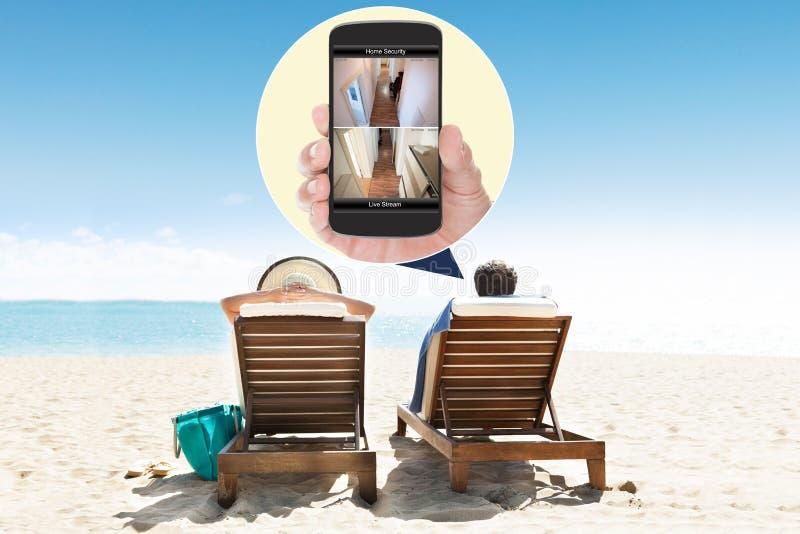 Uomo con la moglie che esamina sistema di sicurezza sul telefono cellulare fotografie stock libere da diritti